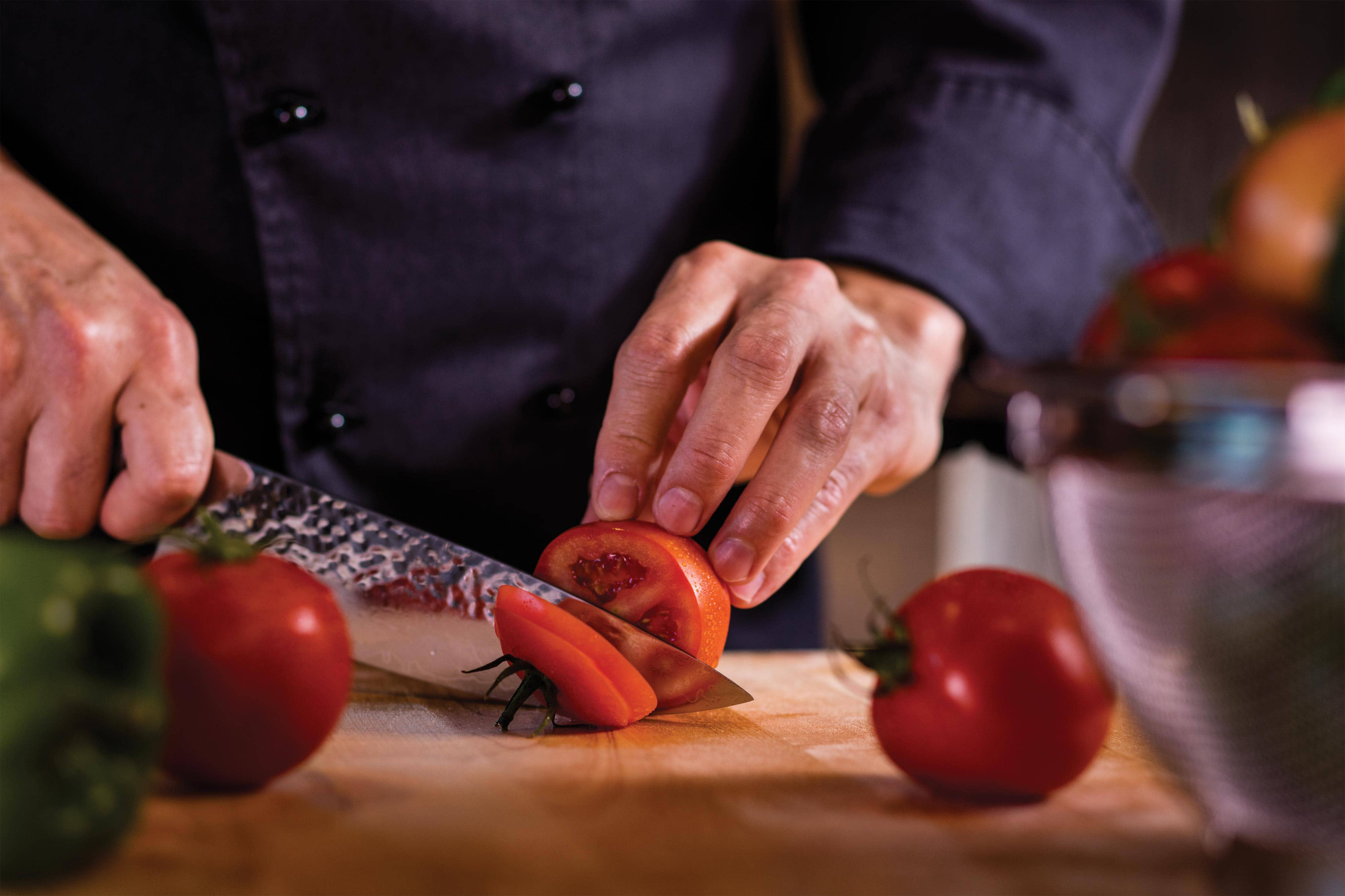Pizza Cucina Chef slicing tomatoes